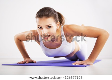 Young woman doing push ups on a mat - stock photo