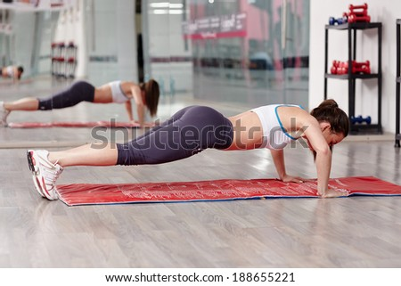 Young woman doing push-ups on a mat in a modern gym - stock photo