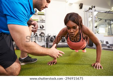 Young woman doing push ups under supervision of a trainer - stock photo
