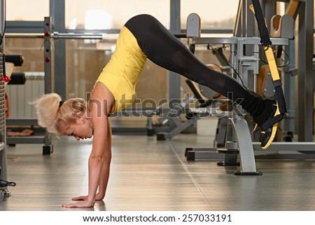 Young woman doing push-ups while legs hanging on elastic rope - stock photo