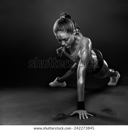 Young Woman Doing Push-Ups workout fitness posture body building exercise exercising on studio - stock photo