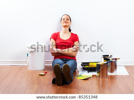 Young woman doing renovation interior wall of home. - stock photo