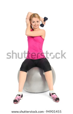 Young woman doing Seated Dumbbell One Arm Triceps Extensions on Fitnes Ball, phase 1 of 2. - stock photo