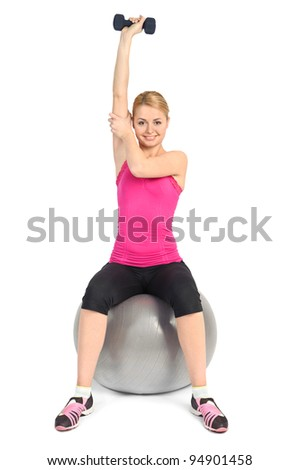 Young woman doing Seated Dumbbell One Arm Triceps Extensions on Fitnes Ball, phase 2 of 2. - stock photo