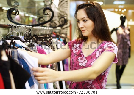 Young woman doing shopping and choosing clothes - stock photo