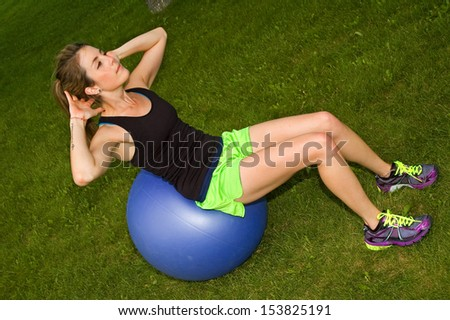 Young woman doing sit ups in a park on an exercise ball.