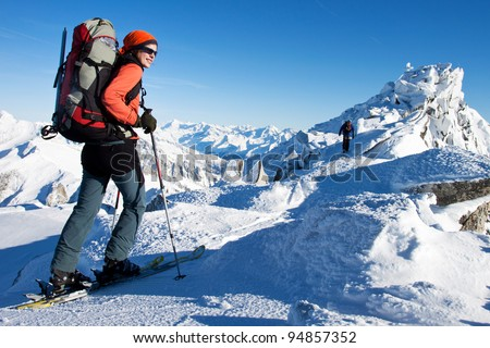 Young woman doing ski touring in winter Alps - stock photo
