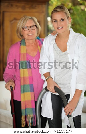Young woman doing some vacuuming for a senior - stock photo