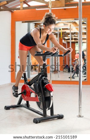 Young woman doing sport spinning in the gym for fitness - stock photo