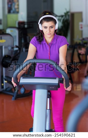 young woman doing sport spinning with headset in the gym - stock photo