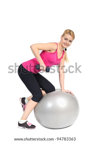 Young woman doing Standing Bent-Over Dumbbell Triceps Extension on Fitness Ball, phase 1 of 2. - stock photo