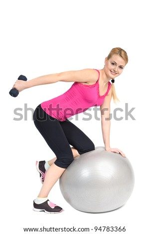 Young woman doing Standing Bent-Over Dumbbell Triceps Extension on Fitness Ball, phase 2 of 2. - stock photo