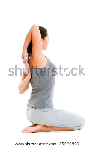 young woman doing stretch exercise in grey clothes. isolated on white background - stock photo