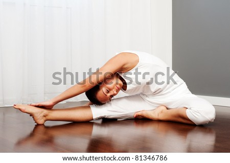 young woman doing stretch exercise on floor - stock photo