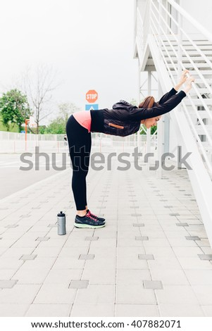 Young woman doing stretching exercises before running in the city - stock photo