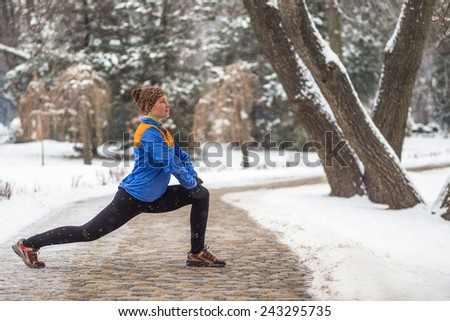 Young woman doing stretching exercises during winter training outside in cold snow weather in park  - stock photo