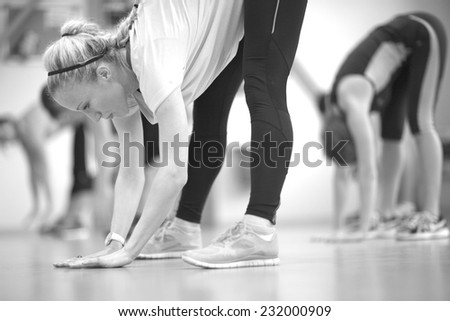 Young woman doing stretching exercises, monochrome - stock photo