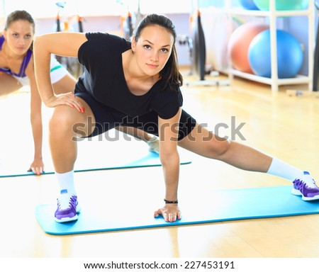 Young woman doing stretching exercises on the floor at the gym - stock photo