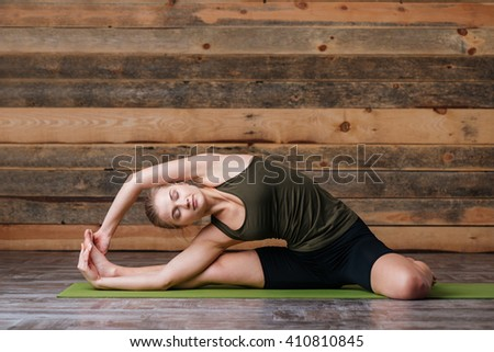 Young woman doing stretching exercises on yoga mat - stock photo