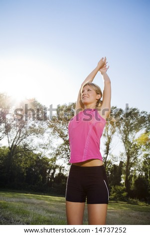 Young woman doing stretching outdoors, copy space - stock photo