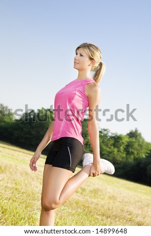 Young woman doing stretching outdoors. copy space - stock photo