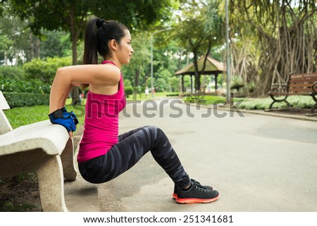 Young woman doing triceps bench dips in the park, side view - stock photo