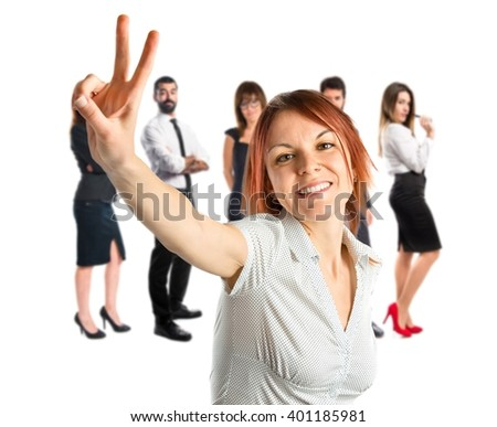 Young woman doing victory gesture over white background  - stock photo