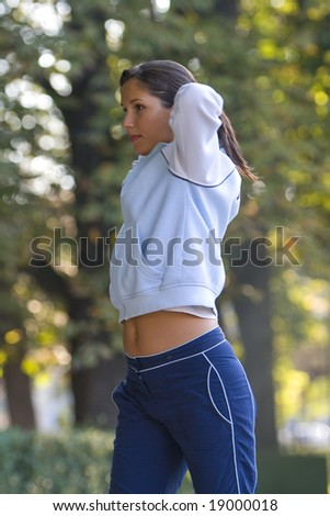 Young woman doing warming-up movements in a park. - stock photo
