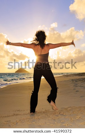 young woman doing yoga and stretches on the beach in Hawaii at sunrise