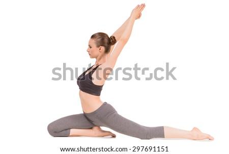 Young woman doing yoga asana in pigeon pose. - stock photo
