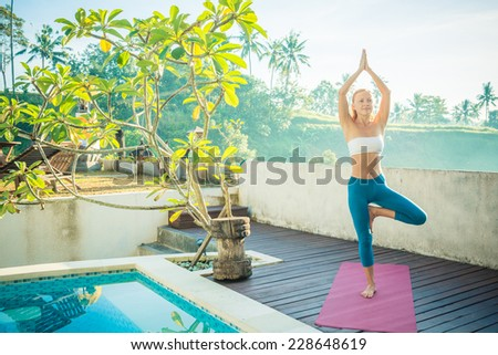 Young woman doing yoga asana in the morning near pool - stock photo