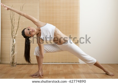 Young woman doing yoga at home/gym - stock photo