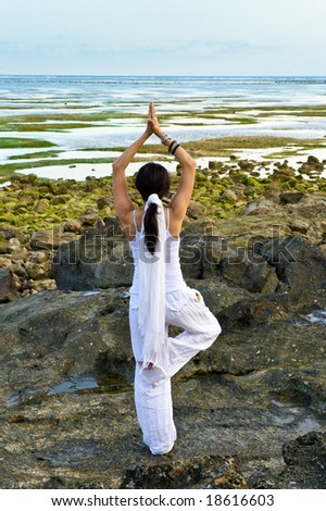 young woman doing yoga at the beach - stock photo