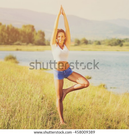 Young woman doing yoga by the lake in summer. Beautiful fit young sporty girl in blue shorts and white tank top practicing yoga in nature on sunny day. Square format, filter applied.