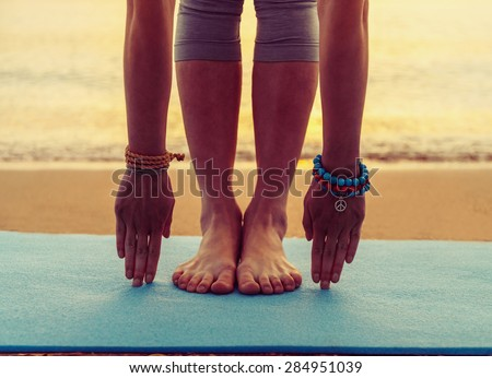 Young woman doing yoga exercise on beach near the sea at sunset in summer, face is not visible - stock photo