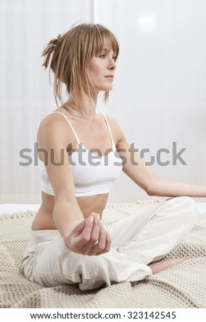 Young woman doing yoga exercise on bed in morning