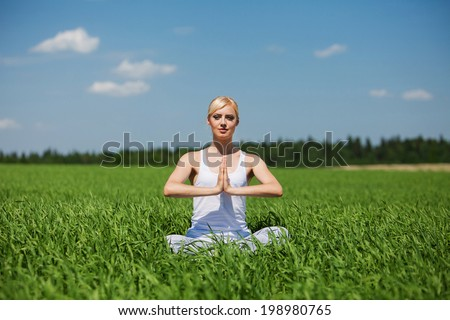 young woman doing yoga exercise on field. Yoga concept.