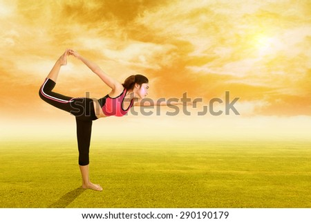 Young woman doing yoga exercise on grass with sky at sunset - stock photo