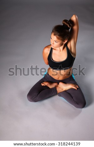 Young woman doing yoga exercise on gray background - stock photo