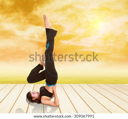 Young woman doing yoga exercise on wood floor with field at sunset