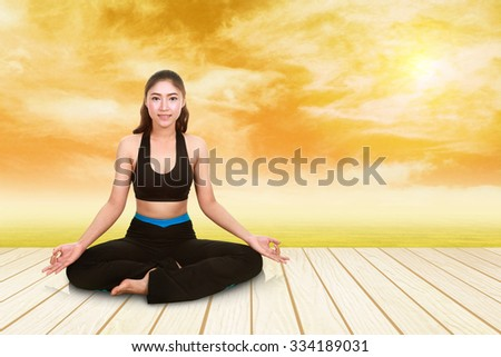 Young woman doing yoga exercise on wood floor with field at sunset - stock photo