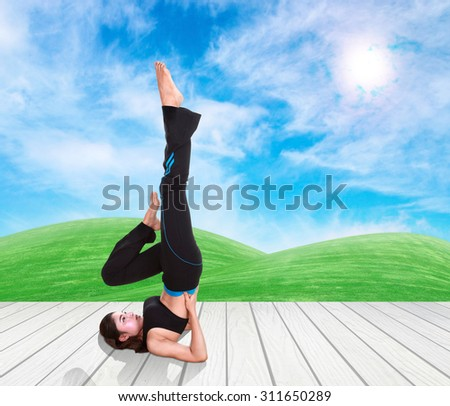 Young woman doing yoga exercise on wood floor with green grass and sky - stock photo