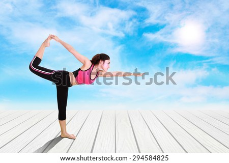Young woman doing yoga exercise on wood floor with sky - stock photo