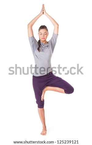 Young woman doing yoga exercise tree-pose isolated on white background - stock photo