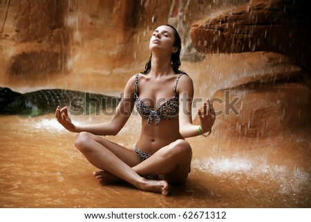 Young woman doing yoga exercise under waterfall - stock photo