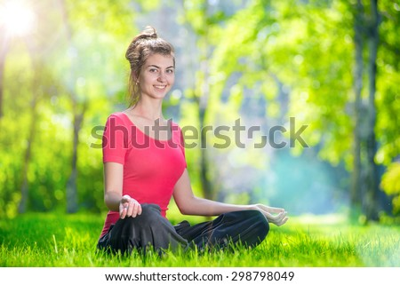 Young woman doing yoga exercises at the summer green city park. In the lotus posture close up