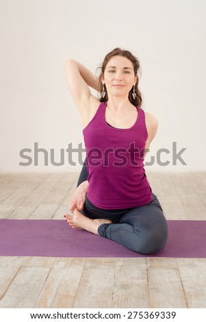 Young woman doing yoga exercises in fitness studio