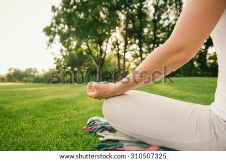 Young woman doing yoga exercises in the nature on sunset