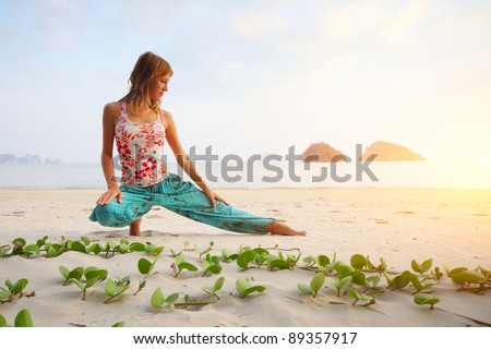 Young woman doing yoga exercises on a beach - stock photo