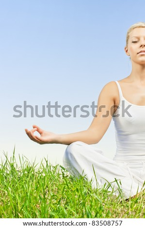 Young woman doing yoga exercising outdoors with copyspace.